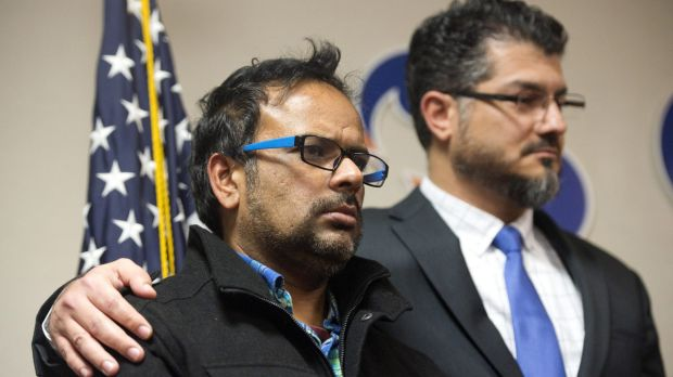 Farhan Khan, left, brother-in-law of one of the suspects involved in a shooting in San Bernardino, California, is held ...