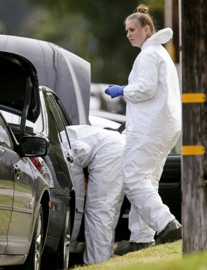 FBI agents investigate a car near a home in connection to the shootings in San Bernardino, California.