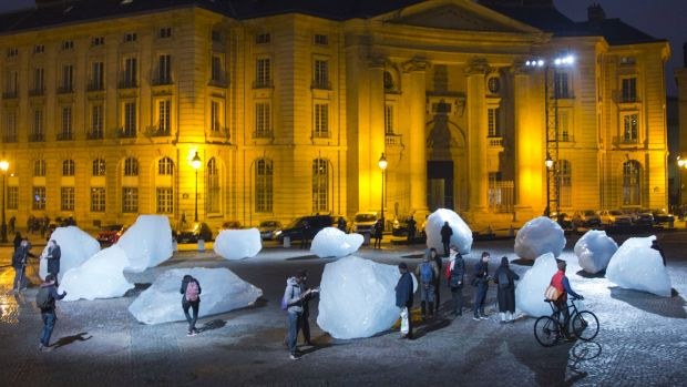 Visitors walk through ice blocks as part of the sculpture Ice Watch, by Danish artist Olafur Eliasson, as part of the ...