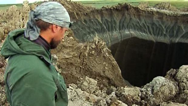 Andrei Plekhanov, a senior researcher at the Scientific Research Center of the Arctic, stands at a crater, discovered ...