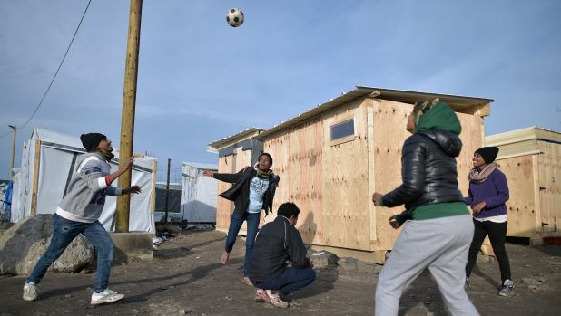 "Migrants play handball in the camp known as the ""New Jungle"" in Calais on December 3."