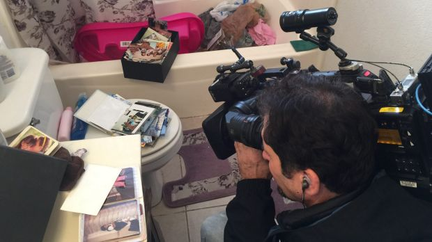 A cameraman films photo albums scattered on top of the toilet in the apartment.