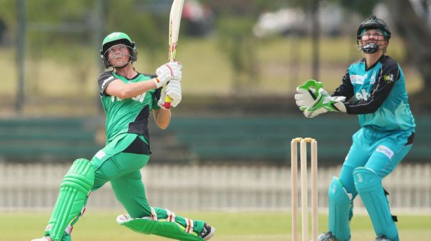 Meg Lanning of the Stars hits a six as Beth Mooney of the Heat looks on.