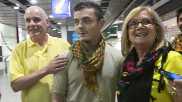 Scott and Julia Dyball greet their son Ashley who returned to Melbourne after fighting Islamic State.