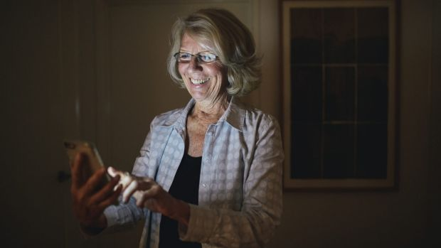 Canberra Uber driver Ulli Brunnschweiler checks on traffic near her home via her smartphone.