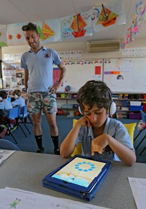 Teacher Matt Serres watches on as grade 1 student Niv Braverman uses the maths  app at Tucker Road Primary.  It works on ...