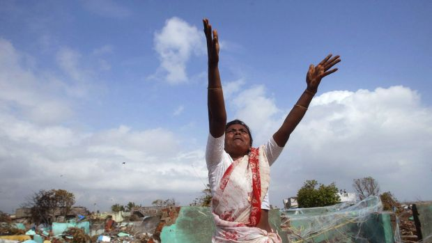 A local fisherwoman gestures for assistance to a hovering navy helicopter in the southern Indian state of Tamil Nadu ...