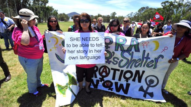 Yaping Wang holds a sign at a rally on the lawns of Parliament House to remember women who lost their lives to domestic ...