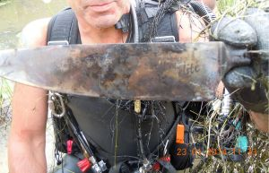 A police diver holds one of the knives recovered from the dam.
