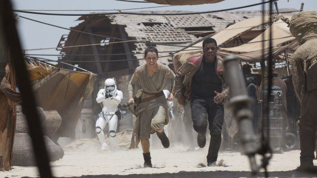 A stormtrooper chases Rey (Daisy Ridley) and Finn (John Boyega) in Star Wars: The Force Awakens.