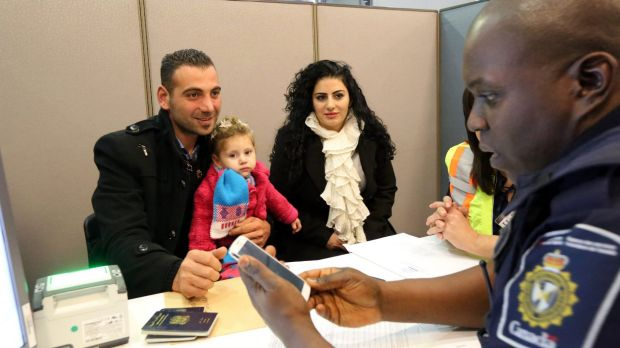 Border Services Officer processes a Syrian refugee family at Toronto Pearson International Airport.