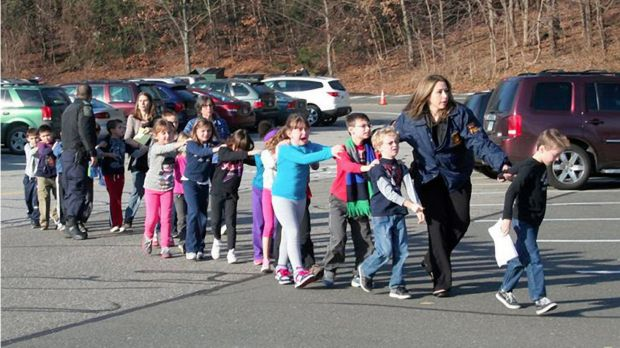 State police personnel lead children from Sandy Hook Elementary School three years ago.