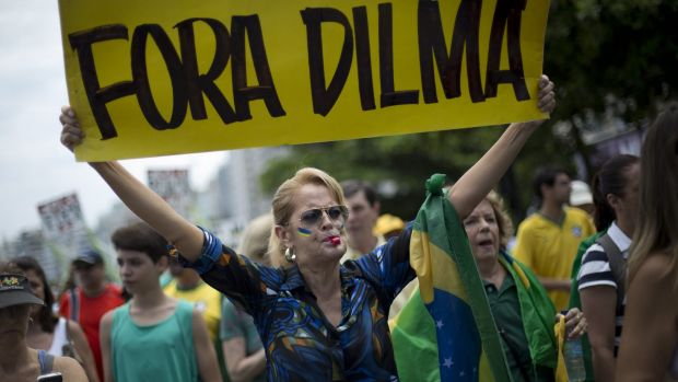 """A woman holds a sign that reads """"Dilma Out"""" during a demonstration for the impeachment of Brazil's President Dilma ..."""