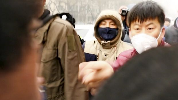 Plain-clothes Chinese police (in masks) face off with foreign journalists covering the trial of Pu Zhiqiang outside ...