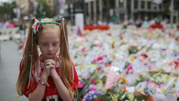 One year anniversary: A young girl dressed in Christmas attire walks around the thousands of floral tributes left in ...