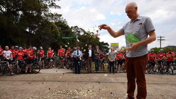 Andrew Zoerner, the father of Nicholas Ruygrok's fiancee, drops rose petals at the site of the fatal crash as members of ...