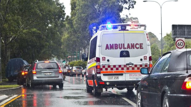 An ambulance battles chaotic traffic on South Dowling Street, Moore Park.