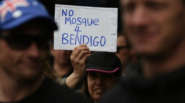 A woman holds a sign during an anti-mosque rally in August 2015.