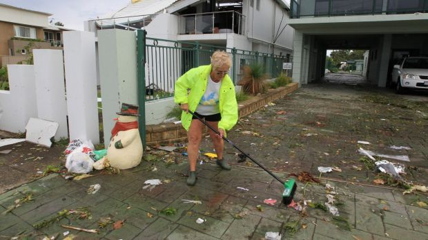 Beverley Bultitude cleans up debris outside her home in Kurnell.