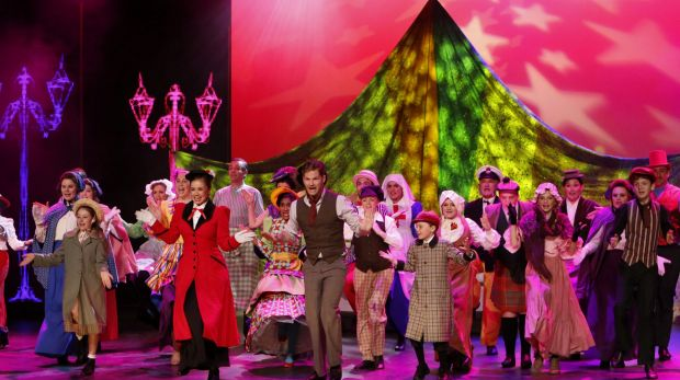 Alinta Chidzey (in red) as Mary Poppins and Shaun Rennie (in brown, with neckscarf) as Bert.