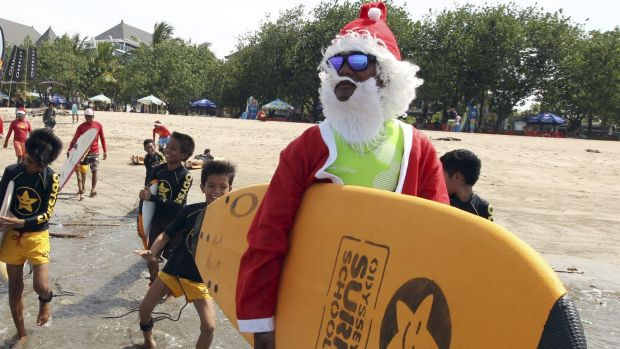 An Indonesian surf instructor dressed as Santa Claus at Kuta beach in Bali, Indonesia.