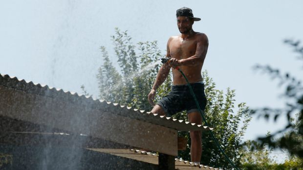 Wandin resident Ricky Booth hoses down his friend's roof.