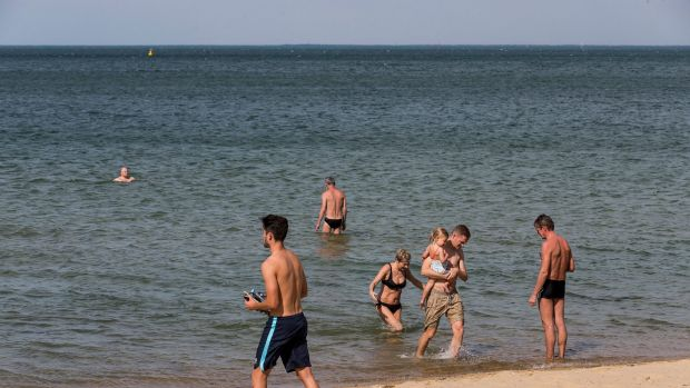 People cooling off in the water at St Kilda Beach on Sunday.