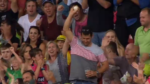 Howzat? A fan displays the ball after taking a one-handed catch without spilling his beer during the Thunder-Sixers Big ...