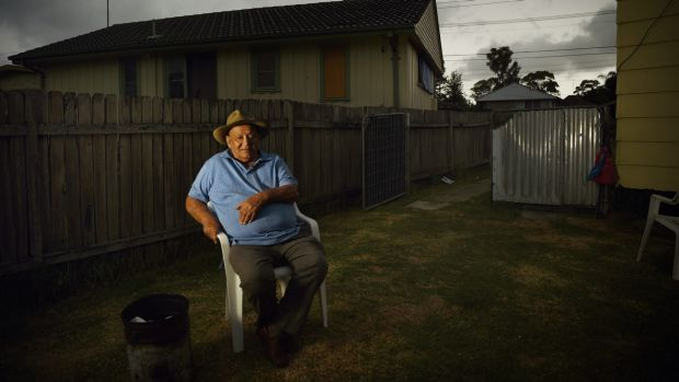 Indigenous elder Uncle Wes Marne sits by his fire bucket in his backyard in Blackett, Sydney.