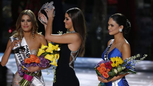 Former Miss Universe Paulina Vega, centre, removes the crown from Miss Colombia Ariadna Gutierrez, left, before giving ...