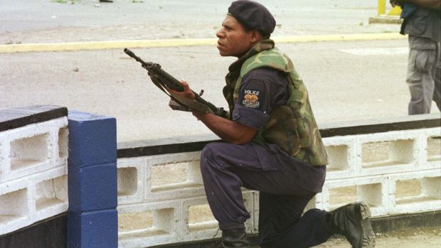 A riot policeman takes cover outside Murray Army Barracks in Port Moresby.