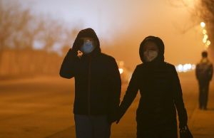 Moves to fight pollution: People walk wearing masks on a heavy pollution evening in Beijing.