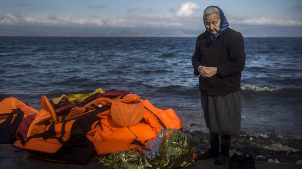 A local stands next to a pile of discarded life jackets after the arrival of refugees and migrants to the Greek island ...