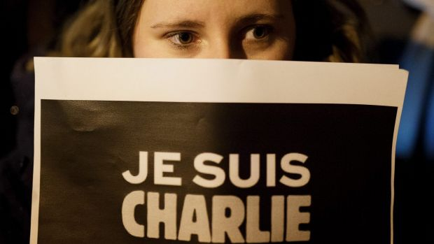 "A woman holds a placard reading ""Je Suis Charlie"" (I am Charlie) during a gathering in Spain for the victims of the ..."