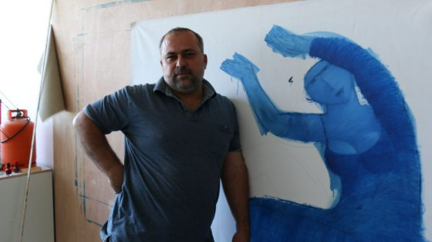 Palestinian artist Ayman Eissa, 41, with one of his unfinished works.