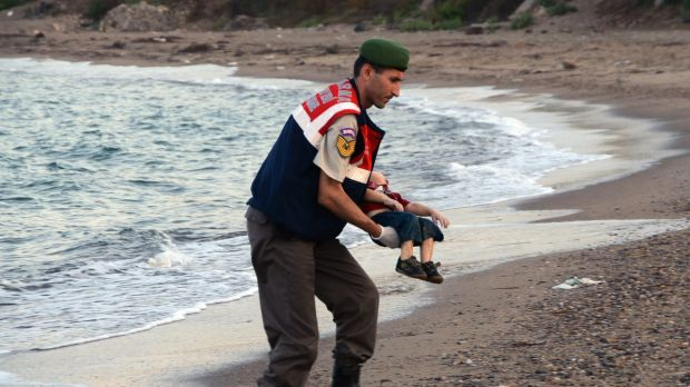 A paramilitary police officer carries the lifeless body of Aylan Kurdi, 3, after a number of migrants died and others ...