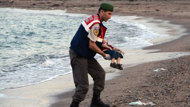 A paramilitary police officer carries the lifeless body of Alan Kurdi. The infant's death sparked an outpouring of ...