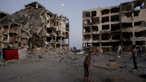 A Palestinian plays in a courtyard near destroyed buildings at a residential neighbourhood in Beit Lahiya, northern Gaza ...