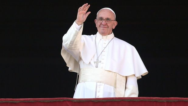 Pope Francis waves to the faithful as he delivers his 'Urbi et Orbi' blessing.