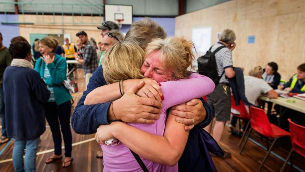 Wye River locals comfort each other at the Apollo Bay Relief Centre.