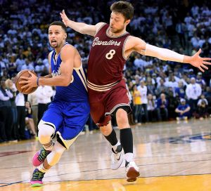 Shadowing: Matthew Dellavedova plays close defence on Steph Curry on Christmas Day.
