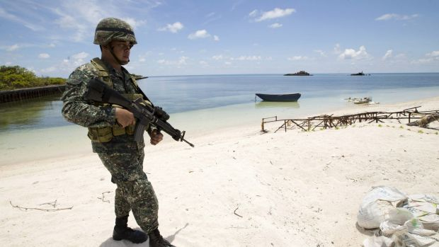 A Filipino soldier patrols the shore of Pagasa Island in the Spratly Islands in May.
