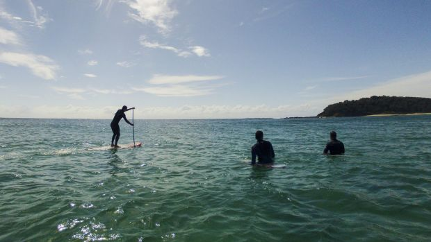 Stand up paddle boarders and surfers at Lake Tabourie on the South Coast of NSW.