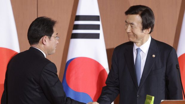 South Korean Foreign Minister Yun Byung-Se (right) shakes hands with Japanese Foreign Minister Fumio Kishida after a ...