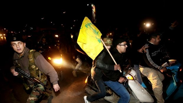 A Lebanese army soldier crosses a street past Hezbollah supporters at the Rafik Hariri International Airport in Beirut.