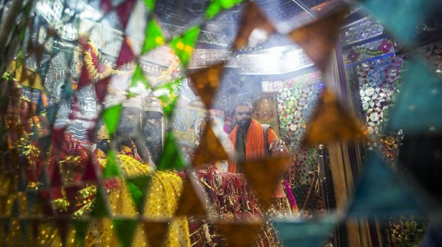 A devotee reflected in a mirror at a temple that stands at a site purported to have been the banks of the mystical ...
