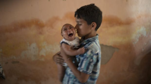 Ten-year-old Elison nurses his two-month-old brother Jose Wesley at their house in Poco Fundo, Pernambuco state, Brazil.