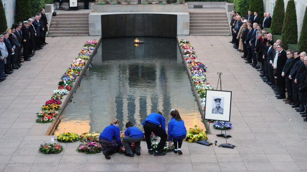 Wreaths are laid near the Pool of Reflection at the Australian War Memorial during a Last Post ceremony.