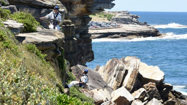 Police abseil down the cliff to the woman's body.