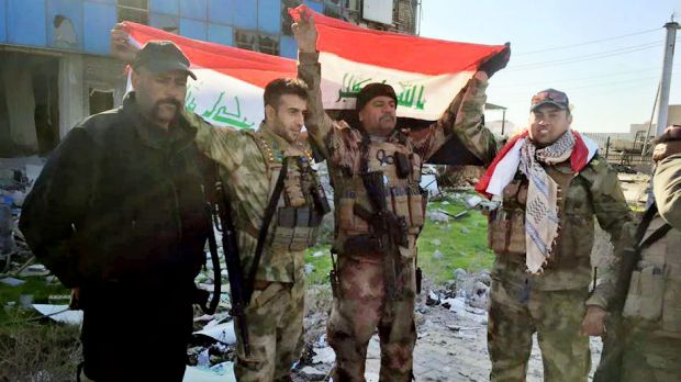 Iraqi soldiers hold national flags in the government complex in central Ramadi.